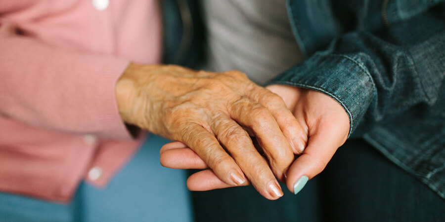 woman holding older woman's hand