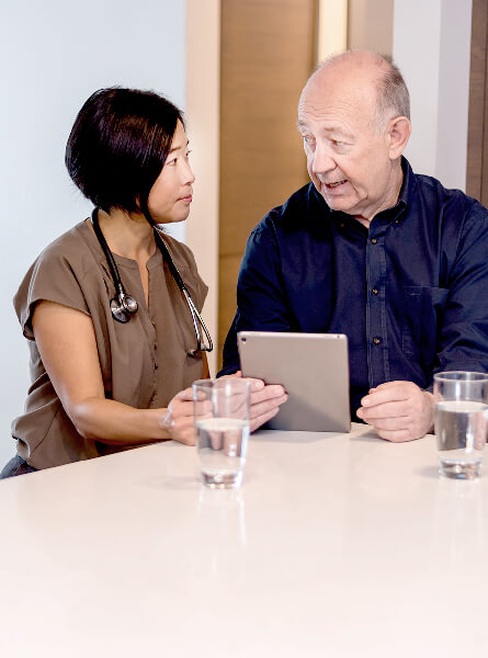 Nurse and man looking at an ipad